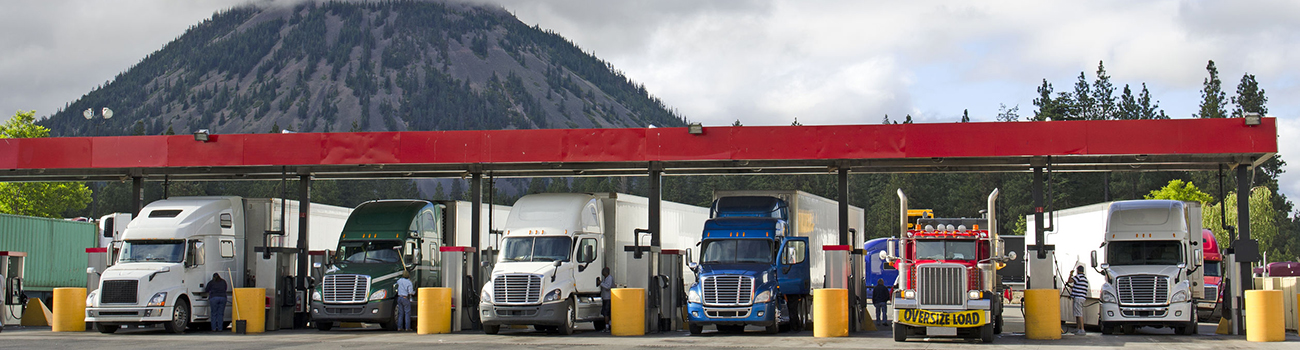 33248308 - several large over the road semi-trucks fuel up at a fueling station truck stop in california